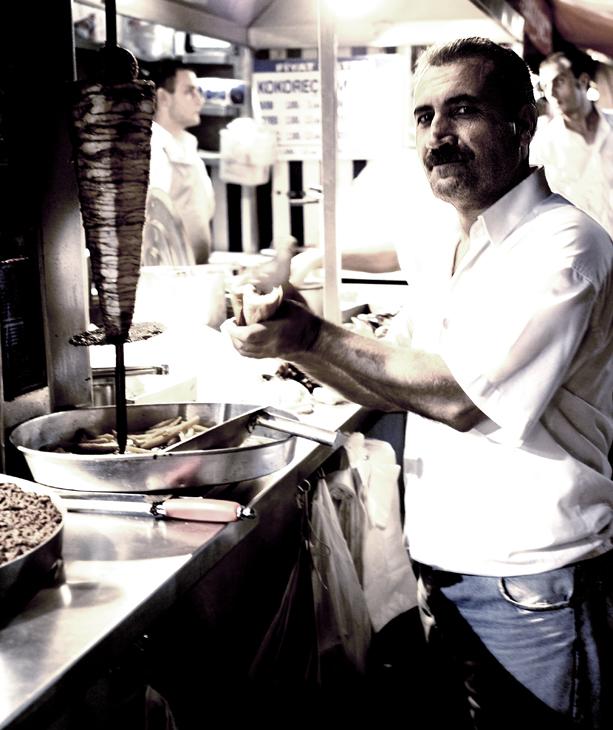 Man Cutting Chicken Meat On Skewer